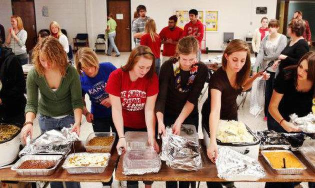 Students remove covers from dishes as food is ready to be served at a holiday meal prepared by Southern Nazarene University student for the Putnam City West High School community. PHOTO BY JIM BECKEL, THE OKLAHOMAN  JIM BECKEL - THE OKLAHOMAN