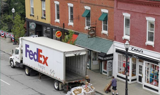 FILE- In this Wednesday, May 23, 2012, file photo, a Federal Express truck makes a delivery in downtown Chagrin Falls, Ohio. FedEx Corp. says the global economy is worsening and it's cutting its forecast for the fiscal year ending in May. The world's second largest package delivery company says profit in the current quarter will be well below year ago results. (AP Photo/Amy Sancetta, File)