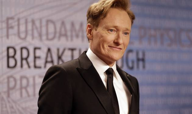 """FILE - In this Dec. 12, 2013, file photo, talk show host Conan O'Brien arrives for the Breakthrough Prize in Life Sciences awards in Moffett Field, Calif. TBS says Conan O'Brien will be sticking around with his late-night hour through 2018. """"Conan"""" premiered on TBS in November 2010. It airs Monday through Thursday at 11 p.m. Eastern time. (AP Photo/Ben Margot, file)"""