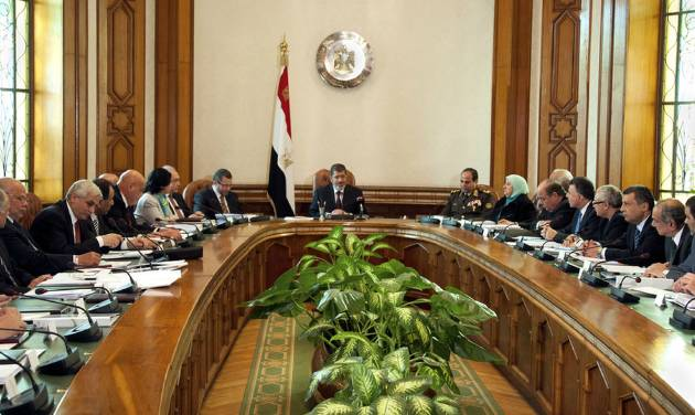 In this image released by the Egyptian Presidency, President Mohammed Morsi, center, meets with his cabinet including 10 new ministers after their swearing in at the presidential palace in Cairo, Egypt, Sunday Jan. 6, 2013. Egypt's government swore in 10 new ministers on Sunday in a Cabinet shake-up aimed at improving the government's handling of the country's struggling economy as foreign reserves levels slid closer to $15 billion, just enough to cover three months' worth of imports. (AP Photo/Egyptian Presidency)