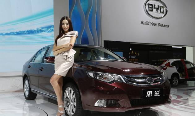 In this Thursday, Nov. 22, 2012 photo, a model poses next to a BYD (Build Your Dream) Si Rui at the company's booth during the Guangzhou 2012 Auto Show in China's southern city of Guangzhou. Chinese automaker BYD Company may be hoping that Si Rui, the name for its new midsize sedan, translates into turnaround. The ailing company, which counts billionaire Warren Buffet as an investor, is banking on the new model to help spur a revival in sales. (AP Photo/Vincent Yu)