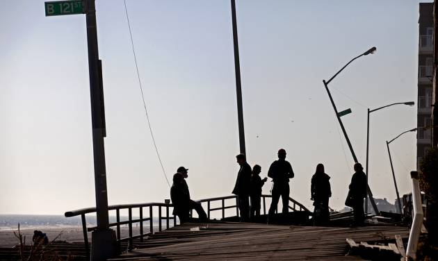 People gather on the buckled boardwalk of the Rockaway Park neighborhood of the borough of Queens, New York, Sunday, Nov. 11, 2012, in the wake of Superstorm Sandy. (AP Photo/Craig Ruttle)