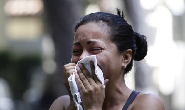 A relative of an inmate taking part of a protest against measures taken by authorities to control a riot at the La Planta prison cries during clashes with National Guard soldiers outside the jail in Caracas, Venezuela, Thursday, May 17, 2012. Gunfire erupted on Thursday inside the prison where armed inmates have prevented security forces from retaking control for nearly three weeks. (AP Photo/Ariana Cubillos)