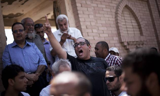 """A friend of Ammar Badie, 38, killed Friday by Egyptian security forces during clashes in Ramses Square, and also son of Muslim Brotherhood's spiritual leader Mohammed Badie, shouts, """"Allah is the greatest,"""" while attending his burial in Cairo's Katameya district, Egypt, Sunday, Aug. 18, 2013. Egypt increased security at the Supreme Constitutional Court building ahead of planned mass rallies by supporters of the country's ousted President Mohammed Morsi. (AP Photo/Manu Brabo)"""