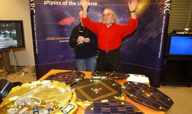 FILE - A Thursday, Dec. 25, 2003 photo from files of Professor Colin Pillinger, leading scientist for the Beagle 2 Mars landing module, gestures in a control centre in central London in front of a model of the 'pod' which landed on Mars as he waits for radio signals from the device. Pillinger, an ebullient British space scientist who captured the popular imagination with his failed attempt to land a probe on Mars, has died. He was 70. Pillinger's family said Thursday that he died at Addenbrooke's Hospital in Cambridge after suffering a brain hemorrhage while sitting in his garden in the university town. (AP Photo/Adam Butler)