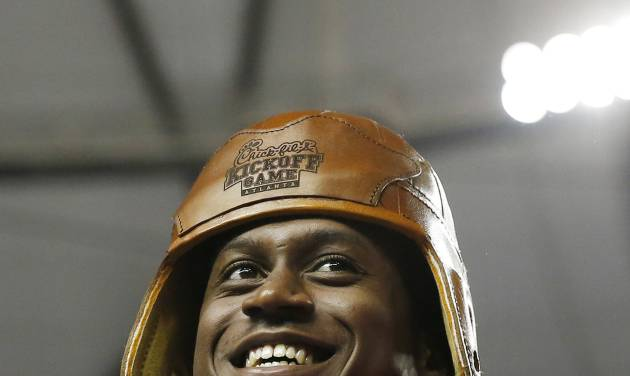 Alabama quarterback Blake Sims (6) wears a replica leather football helmet that is part of the Chick-fil-A kickoff game trophy after defeating West Virginia 33-23 in an NCAA college football game Saturday, Aug. 30, 2014, in Atlanta.  (AP Photo/Brynn Anderson)