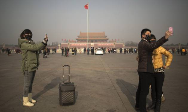 Tourists in masks use mobile phone cameras to snap shots of themselves during a heavily polluted day on Tiananmen Square in Beijing, China, Thursday, Jan. 16, 2014. Beijing's skyscrapers receded into a dense gray smog Thursday as the capital saw the season's first wave of extremely dangerous pollution, with the concentration of toxic small particles registering more than two dozen times the level considered safe. (AP Photo/Alexander F. Yuan)