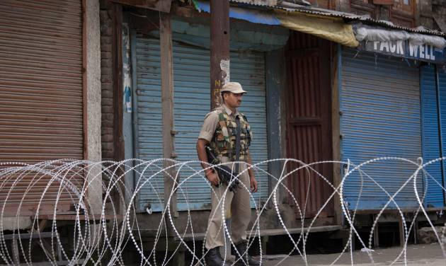 An Indian paramilitary soldier stands guard near a barbed wire set up as road blockade during restrictions in Srinagar, India, Friday, July 4, 2014. Shops, businesses and schools are shut in Indian-controlled Kashmir after separatist groups opposed to Indian rule announced a strike to protest a visit by the country's Prime Minister Narendra Modi. Modi is on his first official visit to the disputed Himalayan region and is expected to inaugurate a railway line and a power station, and also review security and development. (AP Photo/Dar Yasin)