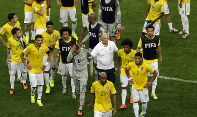 Brazil's coach Luiz Felipe Scolari,center right, and Brazil's goalkeeper Julio Cesar, center left, leave the pitch with other players after  the World Cup third-place soccer match between Brazil and the Netherlands at the Estadio Nacional in Brasilia, Brazil, Saturday, July 12, 2014. Robin van Persie and Daley Blind scored early goals to help give the Netherlands a 3-0 win over host Brazil in the third-place match at the World Cup on Saturday. (AP Photo/Themba Hadebe)