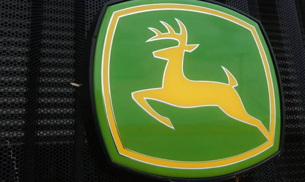 This June 8, 2014 photo shows the John Deere farming logo is seen at a farming equipment dealership in Petersburg, Ill. Deere is laying off about 460 employees indefinitely from an Iowa tractor factory as it continues to adjust to market demand. (AP Photo/Seth Perlman)