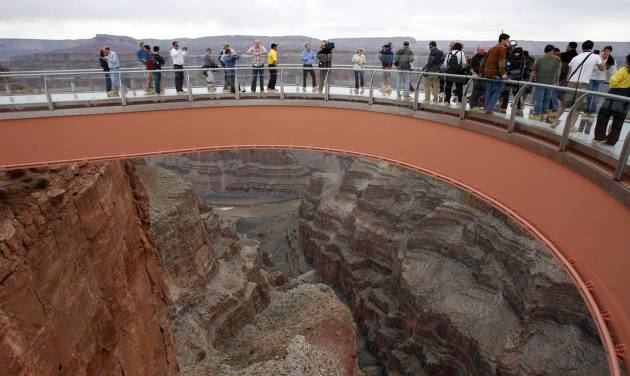 FILE - In this March 20, 2007 file photo, people walk on the Grand Canyon Skywalk on the Hualapai Indian Reservation in Grand Canyon National Park in Arizona. A ceremony is planned Tuesday, Aug. 12, 2014 to mark completion of a newly-paved road which leads to the Skywalk. Known as the Diamond Bar Road, the once rugged, nine-mile washboard road cost more than $30 million to finish and came after years of legal battles with a local dude rancher. (AP Photo/Ross D. Franklin, File)
