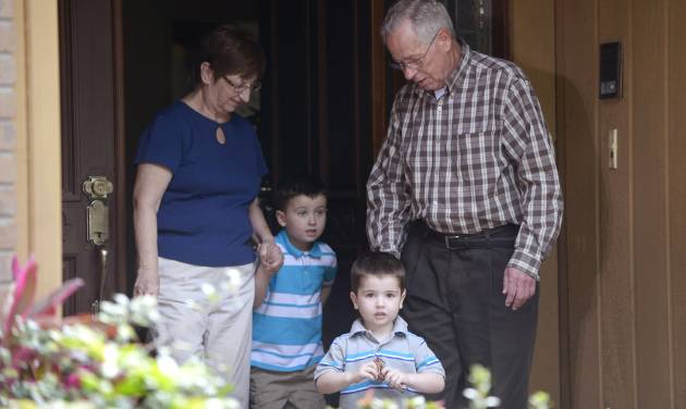 Patricia and Robert Hauser escort their grandchildren, Chase Hakken, 2, second from right, and Cole, 4, out of their house to speak to the media in Tampa, Fla., Thursday, April 11, 2013. The boys were returned to the Hausers, who have legal custody of them, after their parents, Joshua and Sharyn Hakken, kidnapped them and sailed with them to Cuba. The Hakkens were charged with kidnapping the boys and ordered to remain in jail without bond. (AP Photo/Phelan M. Ebenhack)