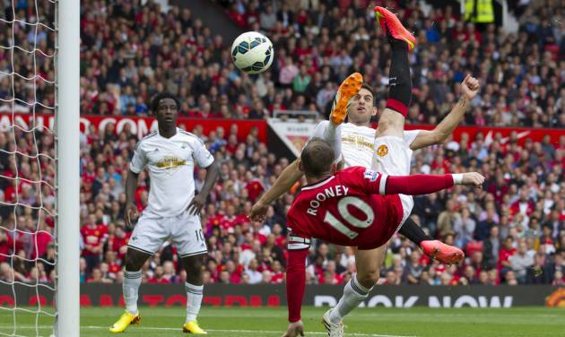 Manchester United's Wayne Rooney, right, scores against Swansea City during their English Premier League soccer match at Old Trafford Stadium, Manchester, England, Saturday Aug. 16, 2014. (AP Photo/Jon Super)