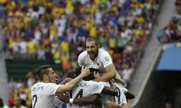 France's Karim Benzema, top, celebrates with teammates including Paul Pogba, bottom right, after Pogba scored their side's first goal during the World Cup round of 16 soccer match between France and Nigeria at the Estadio Nacional in Brasilia, Brazil, Monday, June 30, 2014. France won 2-0 to reach the World Cup quarterfinals. (AP Photo/Ricardo Mazalan)