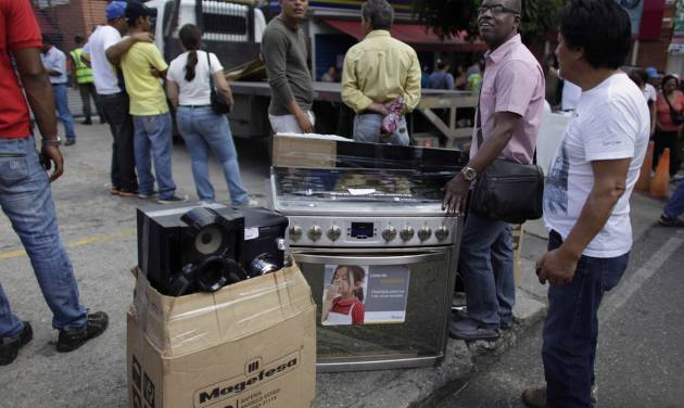 """People stand with their recently purchased goods outside an appliance store in Caracas, Venezuela, Monday, Nov. 11, 2013. President Nicolas Maduro seized control of a nationwide chain of appliance stores Friday seeking to battle inflation and shortages. Shoppers were still arriving Monday to join the hundreds who began amassing over the weekend after price inspectors said they found evidence of """"usury"""" and Maduro ordered the chain Tiendas Daka """"occupation."""" (AP Photo/Ariana Cubillos)"""