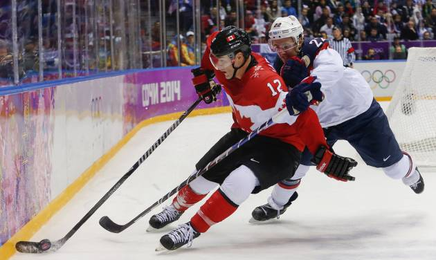 Canada forward Patrick Marleau seals the puck off from USA defenseman Kevin Shattenkirk during the third period of a men's semifinal ice hockey game at the 2014 Winter Olympics, Friday, Feb. 21, 2014, in Sochi, Russia. (AP Photo/Petr David Josek)