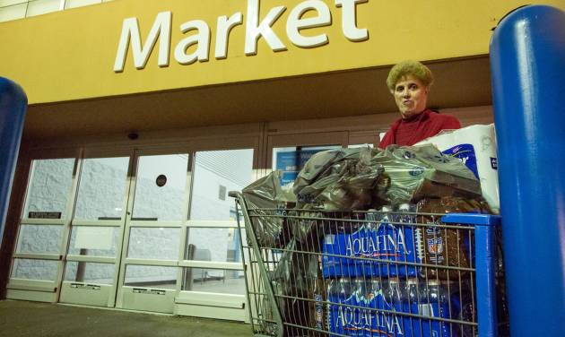 Dora Clark of Charleston, W.Va. stocks up on bottled water at a supermarket in Charleston, W.Va. on Saturday, Jan. 11, 2014 in the wake of Freedom Industries' chemical spill into the Elk River on Thursday. Customers were allowed to purchase up to four cases of water at a time. As many stores ran out, the West Virginia National Guard was sent to bring bottled water to local distribution centers. (AP Photo/Michael Switzer)