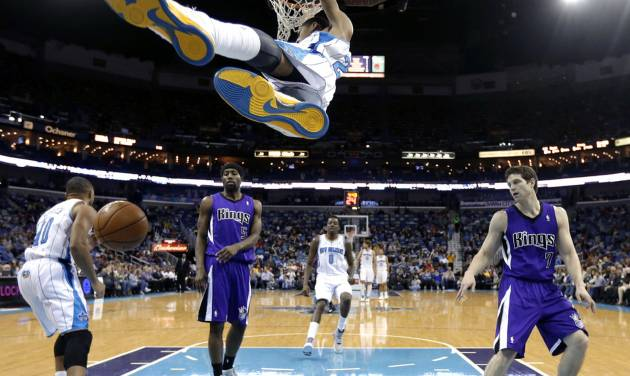 New Orleans Hornets forward Anthony Davis hangs from the rim after slam dunking over Sacramento Kings forward John Salmons (5) and guard Jimmer Fredette (7) in the first half of an NBA basketball game in New Orleans, Sunday, Feb. 24, 2013. (AP Photo/Gerald Herbert)