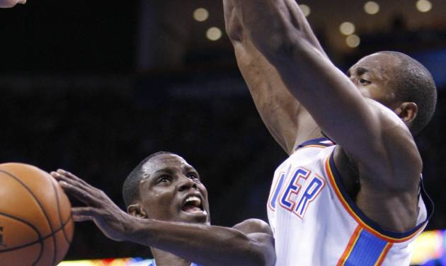 Dallas Mavericks guard Darren Collison, left, goes to the basket in front of Oklahoma City Thunder forward Serge Ibaka, right, during the first quarter of an NBA basketball game in Oklahoma City, Thursday, Dec. 27, 2012. (AP Photo/Alonzo Adams)