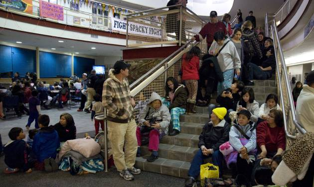 People gather at Sitka High School early Saturday, Jan. 5, 2013, in Sitka, Alaska, following a magnitude 7.5 earthquake and after a subsequent tsunami warning was declared for hundreds of miles of Alaskan and Canadian coastline. The alert was canceled when no damaging waves were generated. (AP Photo/Daily Sitka Sentinel, James Poulson)