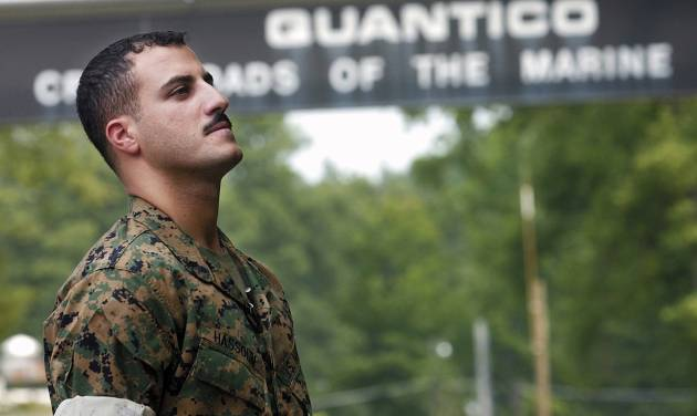 FILE - In this July 19, 2004 file photo USMC Cpl. Wassef Ali Hassoun prepares himself as he waits to make a statement to a large crowd of media outside the gates to USMC Base Quantico, Va. Nearly 10 years ago Hassoun was declared a deserter after allegedly faking his own kidnapping in Iraq, then reappeared and was to face charges. But he disappeared again in 2005, has now turned himself in to U.S. authorities, and is being flown to the U.S. Sunday, June 29, 2014, from an undisclosed Mideast location. Once at Camp Lejeune, the commander of the 2nd Marine Expeditionary Force will determine whether to court-martial him. (AP Photo/Dylan Moore, File)