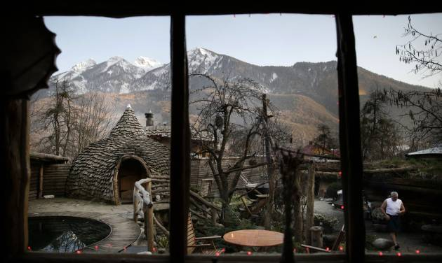"""Bathhouse master Ivan Tkach, right, walks through the outdoor sauna area at the British Banya bathhouse, Saturday, Feb. 15, 2014, in Krasnaya Polyana, Russia. """"The most important thing about the banya is to have a good spirit in the body,"""" Tkach says. (AP Photo/Jae C. Hong)"""