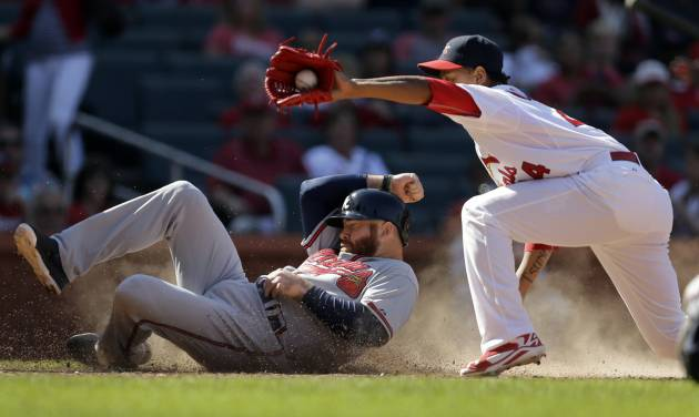 Atlanta Braves' Ryan Doumit, left, scores on a wild pitch by St. Louis Cardinals relief pitcher Carlos Martinez, right, as Martinez covers home during the ninth inning of a baseball game Sunday, May 18, 2014, in St. Louis. (AP Photo/Jeff Roberson)