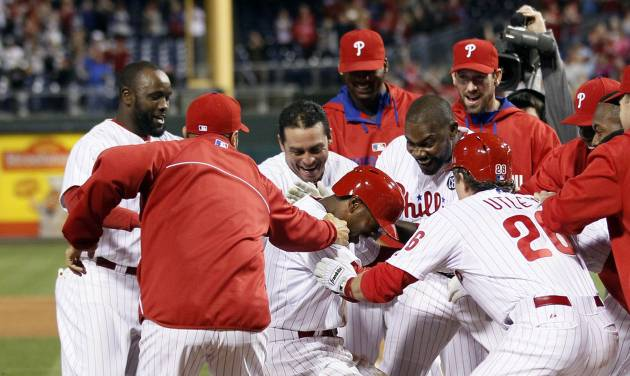 The Philadelphia Phillies surround Jimmy Rollins, center, who hit a solo home run in the bottom of the tenth inning to win a baseball game against the Miami Marlins, Saturday, April 12, 2014, in Philadelphia. The Phillies won 5-4. (AP Photo/Tom Mihalek)