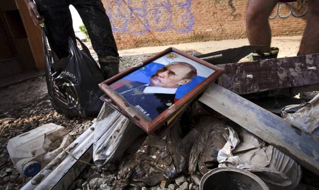 Local residents stand next to a bunch of garbage with a portrait of Russian President Vladimir Putin at a flooded house in Krimsk, about 1,200 kilometers (750 miles) south of Moscow, Russia, Sunday, July 8, 2012. The death toll from severe flooding in the Black Sea region of southern Russia has risen to at least 150. (AP Photo/Ignat Kozlov)