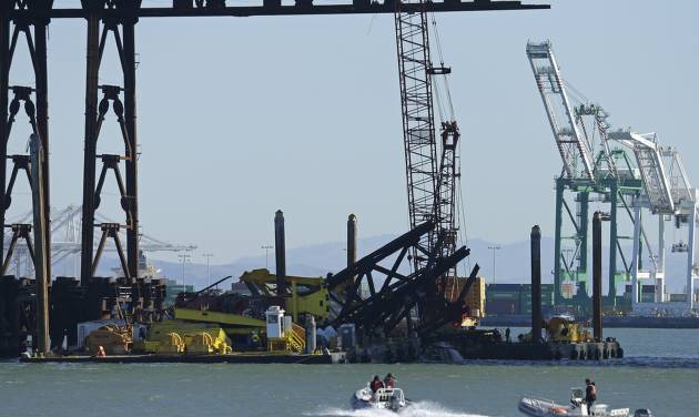 Investigators approach the scene where a crane overturned onto a barge and into San Francisco Bay, seen from Clipper Cove on Treasure Island Thursday, Feb. 21, 2013, in San Francisco. A crane tipped over while working on the new eastern span of the San Francisco-Oakland Bay Bridge on Thursday afternoon, but there were no injuries and nothing leaked into the bay, authorities said. The crane was on a barge underneath the new span helping to remove a temporary support structure and was holding a piece of the structure when it fell around noon Thursday, according to bridge spokesman Andrew Gordon. Gordon said officials are investigating what caused the crane to tip over and whether the new span was damaged at all. The new bridge is expected to open over Labor Day weekend. It will connect Oakland to Treasure Island and replace the eastern span that was damaged during the 1989 Loma Prieta earthquake. (AP Photo/Ben Margot)