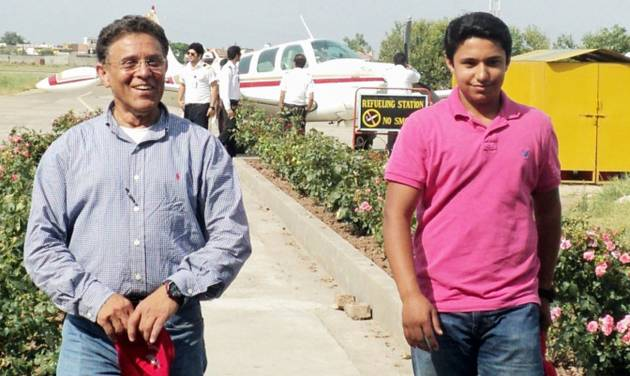 In this July 2014 photo provided by The Citizens Foundation 17-year-old Haris Suleman and his father Babar Suleman, 58, walk away from their single-engine airplane at a stop Islamabad, Pakistan, on their around-the-world flight. The body of the Plainfield, Indiana, teen was recovered after the plane crashed Tuesday, July 22, 2014 shortly after taking off from Pago Pago in American Samoa. Crews were still searching for Babar Suleman. (AP Photo/Courtesy The Citizens Foundation)