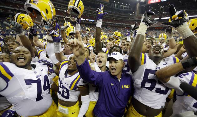 LSU coach Les Miles, center, is surrounded by his team as they celebrate beating Wisconsin in an NCAA college football game Saturday, Aug. 30, 2014, in Houston. LSU won 28-24. (AP Photo/David J. Phillip)