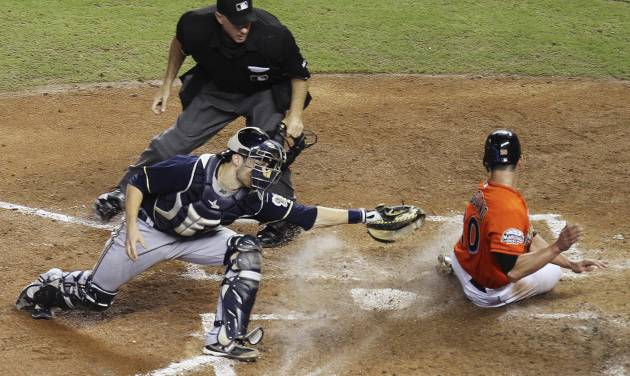 Home plate umpire Paul Emmel watches as Miami Marlins' Justin Ruggiano (20) slides safely past Milwaukee Brewers catcher Jonathan Lucroy (20) during the fourth inning of a baseball game in Miami, Monday, Sept. 3, 2012. (AP Photo/J Pat Carter)