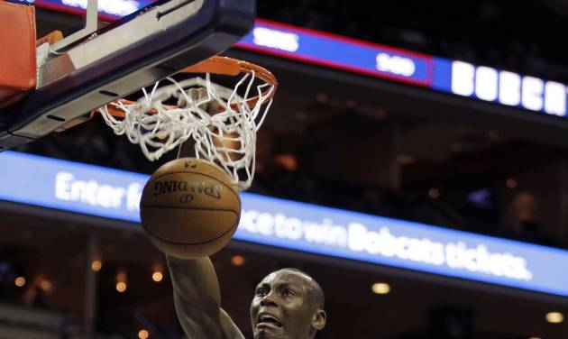 Charlotte Bobcats' Bismack Biyombo (0) dunks past Brooklyn Nets' Brook Lopez (11) during the first half of an NBA basketball game in Charlotte, N.C., Wednesday, March 6, 2013. (AP Photo/Bob Leverone)