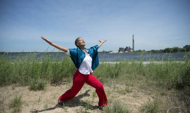 "In this July 1, 2014 photo provided by the Grand Valley State University, Robin Wilson, a University of Michigan dance professor, poses for a photo near the Renewable Energy Center in Muskegon, Mich. Wilson has a solo in the performance of ""Into the Wind,"" a collaboration involving Grand Valley State University, the University of Michigan in Ann Arbor and the Muskegon community on Aug. 22 and 23. (AP Photo/Grand Valley State University, Jeff Dykehouse)"