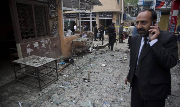 A Pakistani lawyer talks on his mobile phone at the site of a suicide attack in a court complex, Monday, March 3, 2014 in Islamabad, Pakistan. Two suicide bombers blew themselves up at the complex on Monday, killing nearly a dozen and wounding scores in a rare terror attack in the heart of Islamabad, officials said. (AP Photo/B.K. Bangash)