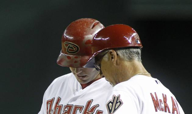 Arizona Diamondbacks' Paul Goldschmidt, left, shows first base coach Dave McKay (39) where he was hit by a pitch during the ninth inning of a baseball game against the Pittsburgh Pirates, Friday, Aug. 1, 2014, in Phoenix. The Pirates defeated the Diamondbacks 9-4. (AP Photo/ Ralph Freso)