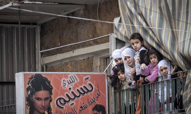 In this Friday, Nov. 30, 2012 photo, Syrian women and children watch a demonstration after Friday prayers in the Bustan Al-Qasr district of Aleppo, Syria. After months of fighting, thousands of residents have returned to the city as they attempt to return to their daily lives while heavy fighting is still taking place along the front lines in the city. Public demonstrations have unfolded after several weeks of silence as residents demand an end to the violence in Aleppo. (AP Photo/Narciso Contreras)