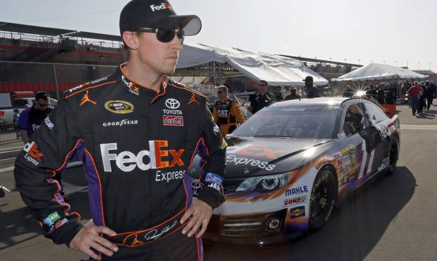Denny Hamlin stands in the garage area after taking the pole position in his FedEx Express Toyota for the NASCAR Sprint Cup series Auto Club 400 auto race in Fontana, Calif., Friday, March 22, 2013. (AP Photo/Reed Saxon)