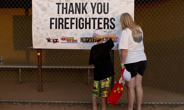 Ten-year-old Lyam Davis, left, watches as his mother, Rachel Davis, both of Phoenix, Ariz., sign a banner during the Fourth of July celebration at Pioneer Park, Thursday, July 4, 2013 in Prescott, Ariz. in honor of the 19 fallen Granite Mountain Hotshot firefighters who died fighting a blaze near Yarnell, Ariz. on Sunday. On a day meant to ponder the nation's birth, and those who built and defended it over 237 years, Prescott's residents had 19 of their neighbors, their friends, their relatives to remember. (AP Photo/Julie Jacobson)