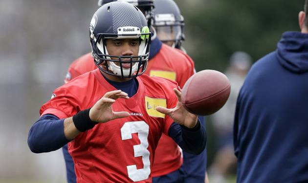 Seattle Seahawks quarterback Russell Wilson reaches for the ball during NFL football practice Thursday, Jan. 16, 2014, in Renton, Wash. The Seahawks play the San Francisco 49ers on Sunday in the NFC championship game. (AP Photo/Elaine Thompson)