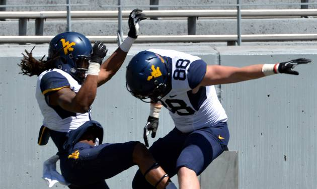 West Virginia's Kevin White (11) celebrates his touchdown with Cody Clay (88) during their spring NCAA college football game in Morgantown, W.Va., Saturday, April 12, 2014. (AP Photo/Craig Cunningham)