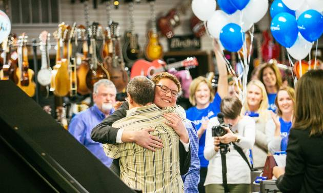 Andrew Vargas, 15, of Mustang, hugs his piano teacher, Greg Fisher, after presenting Fisher with a new Steinway grand piano at Edmond Music, 3400 S Broadway.  [Photo by Jonathan Hane, For The Oklahoman]