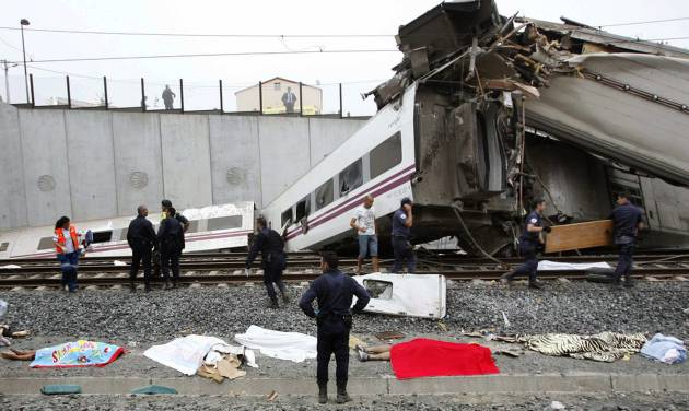 Emergency personnel respond to the scene of a train derailment in Santiago de Compostela, Spain, on Wednesday, July 24, 2013. A train derailed in northwestern Spain on Wednesday night, toppling passenger cars on their sides and leaving at least one torn open as smoke rose into the air. Dozens were feared dead, with possibly even more injured. (AP Photo/ El correo Gallego/Antonio Hernandez)