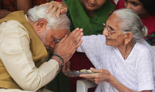 "90-year-old Hiraben blesses her son and India's next prime minister Narendra Modi at her home in Gandhinagar, in the western Indian state of Gujarat, Friday, May 16, 2014. The top official in Gujarat state for over a decade, Modi often contrasted his humble roots with the posh background of his main rival, 43-year-old Rahul Gandhi, heir to India's most powerful political dynasty. As the career politician led his party through a dazzling, high-tech election campaign, Modi called voters' attention to his mother riding a three-wheeled auto-rickshaw to cast her ballot earlier this month. ""I am the chief minister of a prosperous state ... And my 90-year-old mother goes to vote in an auto-rickshaw,"" the white-bearded Modi boasted, punching a fist through the air as he claimed his place by India's poor masses. (AP Photo/Ajit Solanki)"