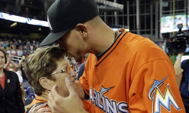 Miami Marlins starting pitcher Jose Fernandez, right, kisses his grandmother Olga Fernandez, of Cuba, left, following the Marlins' 10-1 victory over the Colorado Rockies during an opening day baseball game, Monday, March 31, 2014, in Miami. (AP Photo/Lynne Sladky)