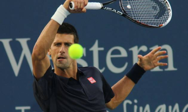 Novak Djokovic, of Serbia, returns a volley to Gilles Simon, of France, at the Western & Southern Open tennis tournament, Tuesday, Aug. 12, 2014, in Mason, Ohio. (AP Photo/Tom Uhlman)