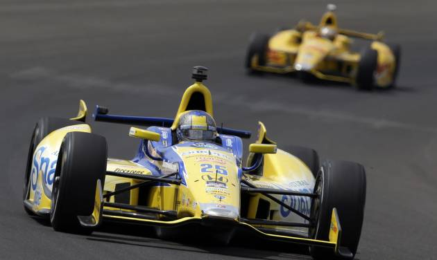 Marco Andretti leads Ryan Hunter-Reay through the first turn during practice for Indianapolis 500 IndyCar auto race at the Indianapolis Motor Speedway in Indianapolis, Monday, May 12, 2014. (AP Photo)