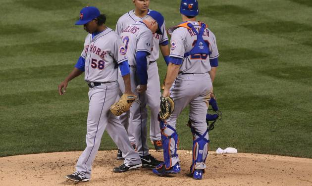 New York Mets starting pitcher Jenrry Mejia, left, steps off the mound after he was pulled by manager Terry Collins, second from left, as shortstop Ruben Tejada, back, and catcher Anthony Recker look on after he gave up a grand slam to Colorado Rockies' Nolan Arenado in the fifth inning of a baseball game in Denver, Saturday, May 3, 2014. (AP Photo/David Zalubowski)
