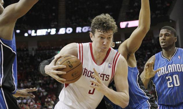 Houston Rockets center Omer Asik (3) grabs an offensive rebound away from Orlando Magic forward Tobias Harris, behind, during the second half of an NBA basketball game Monday, April 1, 2013 in Houston. Houston won 110-103. (AP Photo/Bob Levey)